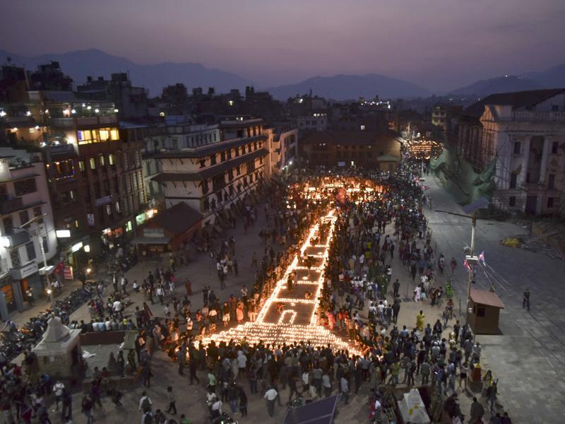 Kathmandu residents lit candles to create the shape of historic nine-storey Dharara tower and Kasthamandap temple to mark the first anniversary of the devastating earthquake that ripped through the Himalayan nation and killed thousands of people. (Raj K Raj/Hindustan Times)