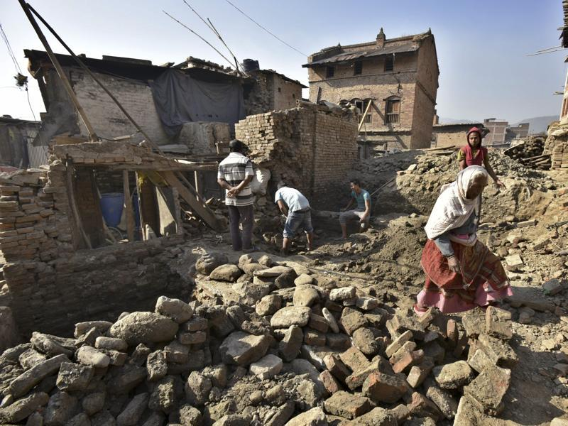 Villagers move through the houses damaged by last year's earthquake.  (Raj K Raj/Hindustan Times)