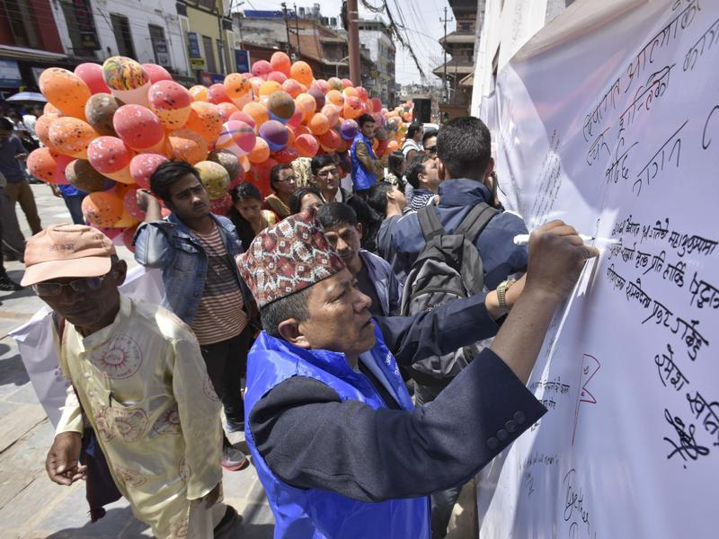 Nepalese people write messages in memory of their loved ones on the first anniversary of the 2015 earthquake at Darbar Square. (Raj K Raj/Hindustan Times)