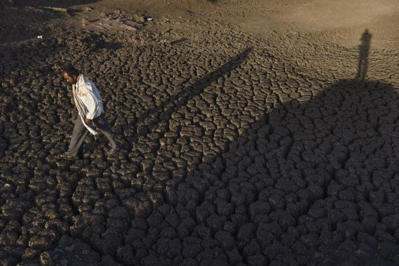 A summer of discontent looms over Maharashtra, with more than 34% of  the state being declared under drought. In Marathwada's Beed village, a man walks across the dried up Bendsura Dam.  (Satish Bate/Hindustan Times)