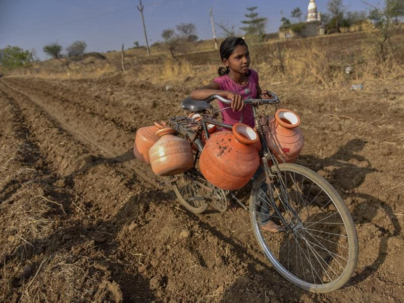 Little girls and boys are forced to miss school so they can fetch water from kilometres away. On April 20, a 12-year-old girl succumbed to the heatwave, after making multiple trips to get water for her family.  (Satish Bate/Hindustan Times)