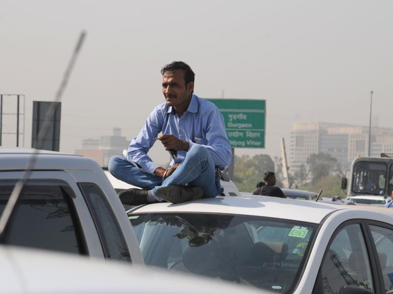 Many of Delhi's taxis already run on CNG, but the ban will impact about 30,000 traditional cabs and some working for app-based Uber and Ola services, according to taxi operators. In this photo, a man waits on the top his car after getting caught  in a traffic jam on Delhi-Gurgaon highway. (Parveen Kumar/HT Photo)
