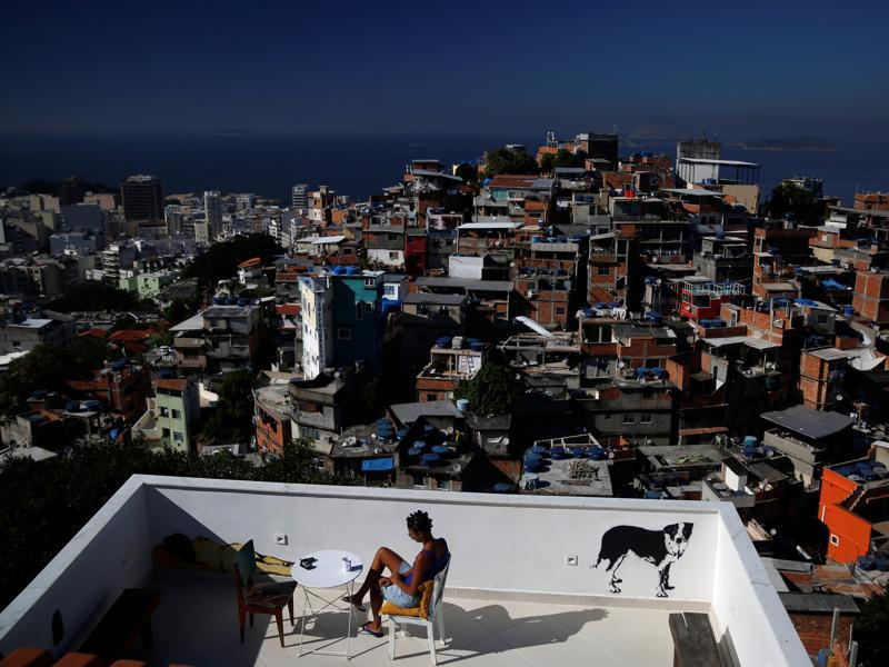 Hostels in a few of Rio's more than 1,000 slums will serve as a cheap housing alternative for the more adventurous among the estimated 500,000 foreign tourists expected to arrive for the Olympics in August. A woman sits on a terrace at Tiki hostel in Cantagalo favela in Rio de Janeiro, Brazil, April 16, 2016. (REUTERS)