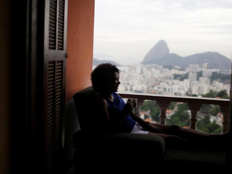 A guest relaxes with the The Sugar Loaf mountain in the background at Pousada Favelinha (Little favela) hostel. (REUTERS)