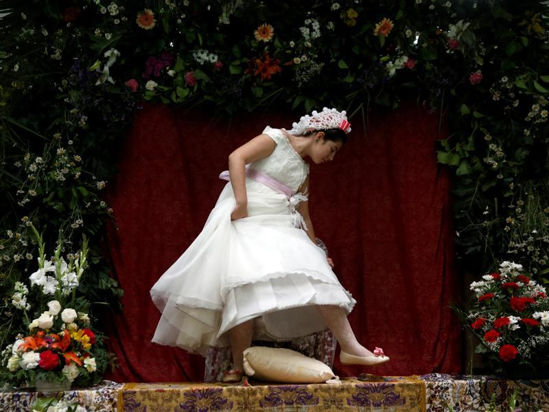 Young girls are chosen to become Mayas and sit at altars decorated with flowers so that people can admire them. Maya girl Lucia Carrillo, 12, leaves the altar for another Maya during Las Mayas festivity. (REUTERS)