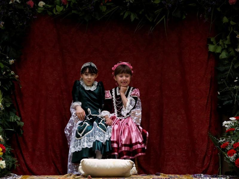 This year the rain forced the Mayas to share an altar indoors, after the ones built on the streets got too wet. Maya girl Ines de la Paloma, 9, (L), sits with her friend Nuria Sanchez Caballero, 6, at an altar. (REUTERS)