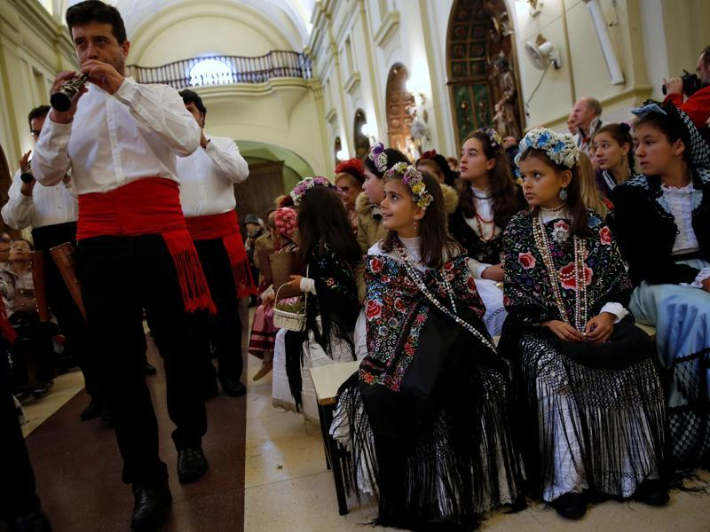 Musicians sing their praises and tell about their beauty while people dance and Maya girl assistants request money in exchange for sweets and flowers. Maya girls and their assistants look at musicians playing at San Lorenzo church during Las Mayas festivity. (REUTERS)
