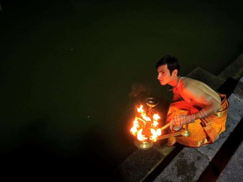 A Hindu priest holds a traditional lamp as he performs evening prayers called