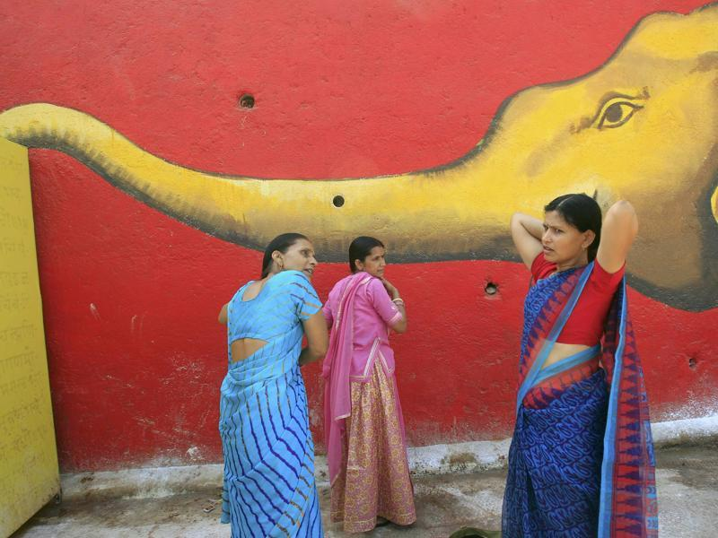 Women comb their hair in front of a mural after taking a holy dip in the Shipra river during Simhastha Kumbh Mela in Ujjain. (REUTERS)
