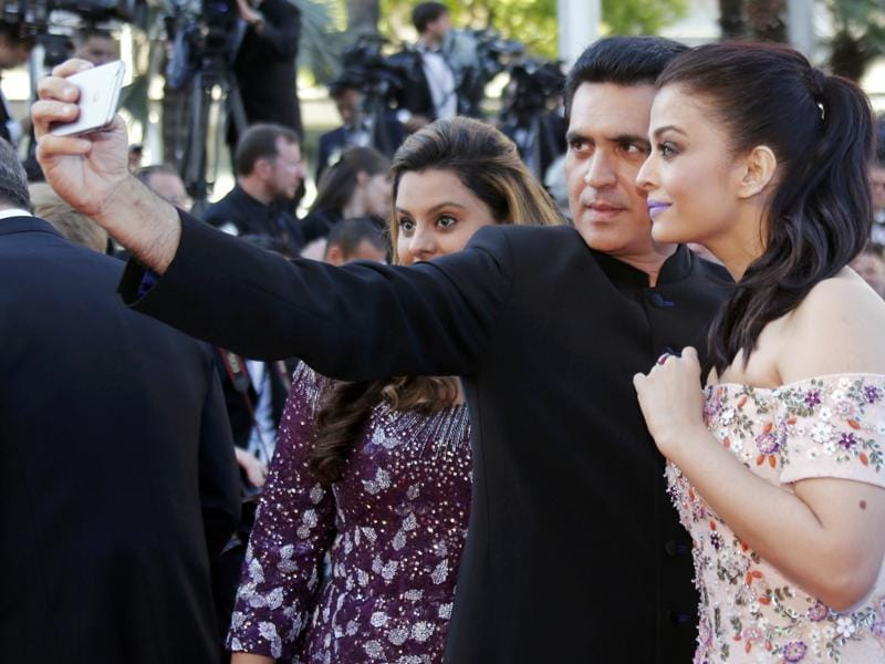 Actor Aishwarya Rai Bachchan (Right) takes a selfie as she poses on the red carpet as she arrives for the screening of the film Mal de pierres with Sarbjit director Omung Kumar . (REUTERS)