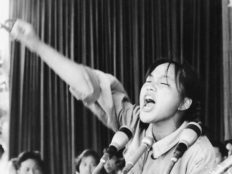 A young woman identified only as Ms. Zhou calls out to embolden her fellow Red Guards in Beijing's Tiananmen Square at the start of the 1966-76 Cultural Revolution.  (AP File Photo)