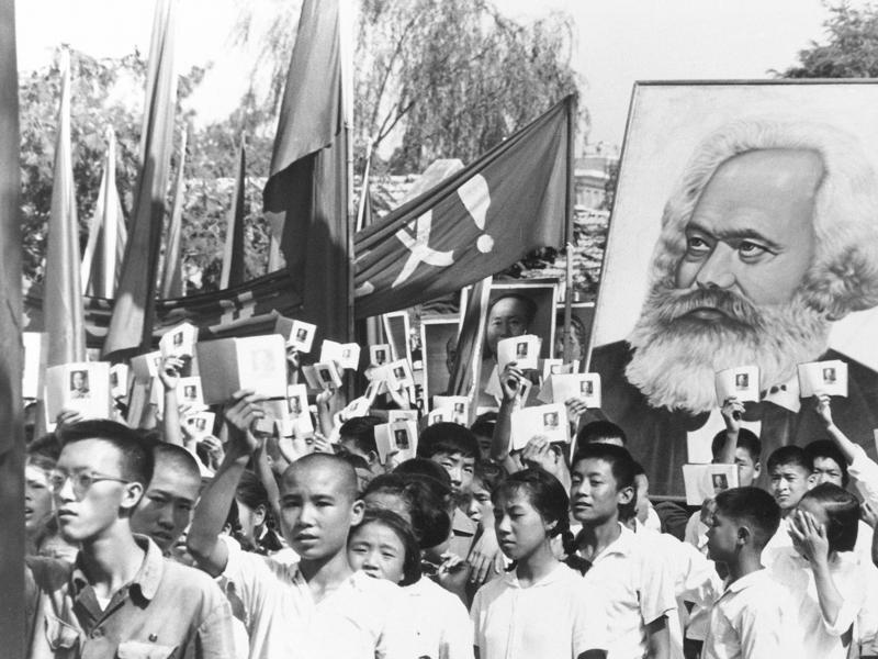 Children are seen at a rally during the height of the Red Guard upheaval, waving copies of the collected writings of Communist Party chairman Mao Zedong, often referred to as Mao's Little Red Book, and carrying a poster of Karl Marx.  (AP File Photo)