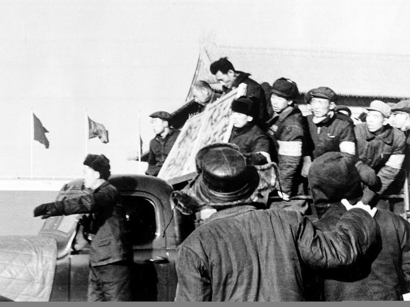 Two men with placards around their necks are declared anti-revolutionary elements and paraded through the streets of Beijing by members of the Red Guard during the early days of the Cultural Revolution. (AP File Photo)