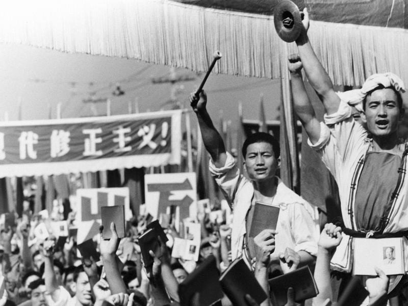 Drummers raise their cymbals and sticks as others hold up small booklets containing the writings of then chairman, Mao Zedong, during a demonstration by Red Guard youth groups in front of the Soviet Embassy in Beijing.  (AP File Photo)