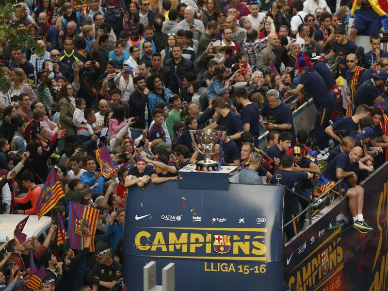 FC Barcelona's players interact with the crowd as the bus passes. (AP)