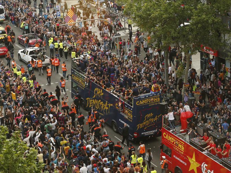 The open-top bus carrying Barcelona's players passes through the streets of the city. (AP)