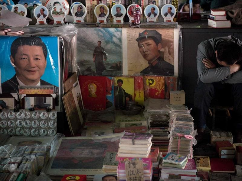 A vendor (right) takes a nap next to posters showing the late Chinese chairman Mao Zedong (centre) and Chinese President Xi Jinping (left) at a market in Beijing. Fifty years after the Cultural Revolution spread bloodshed and turmoil across China, the Communist-ruled country is driving firmly down the capitalist road but Mao Zedong's legacy remains. (AFP File Photo)
