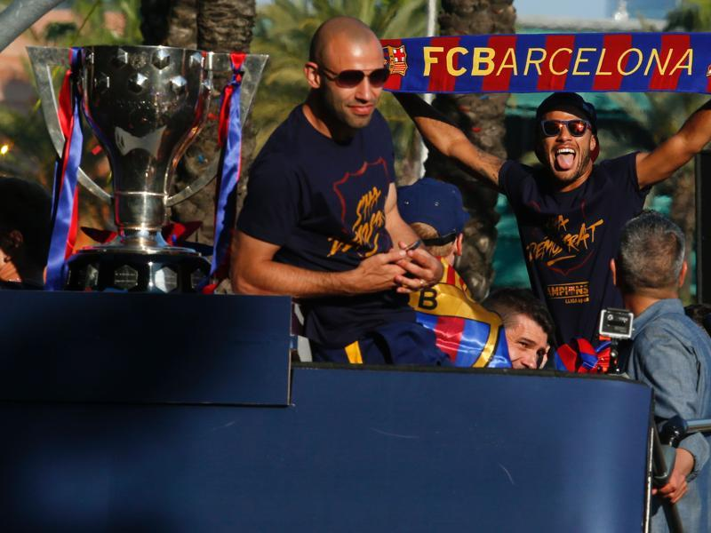 Barcelona's Javier Mascherano (L) and Neymar parade on a bus with their teammates through the streets of Barcelona to celebrate FC Barcelona's 24th La Liga title, in Barcelona, on May 15, 2016. (AFP)