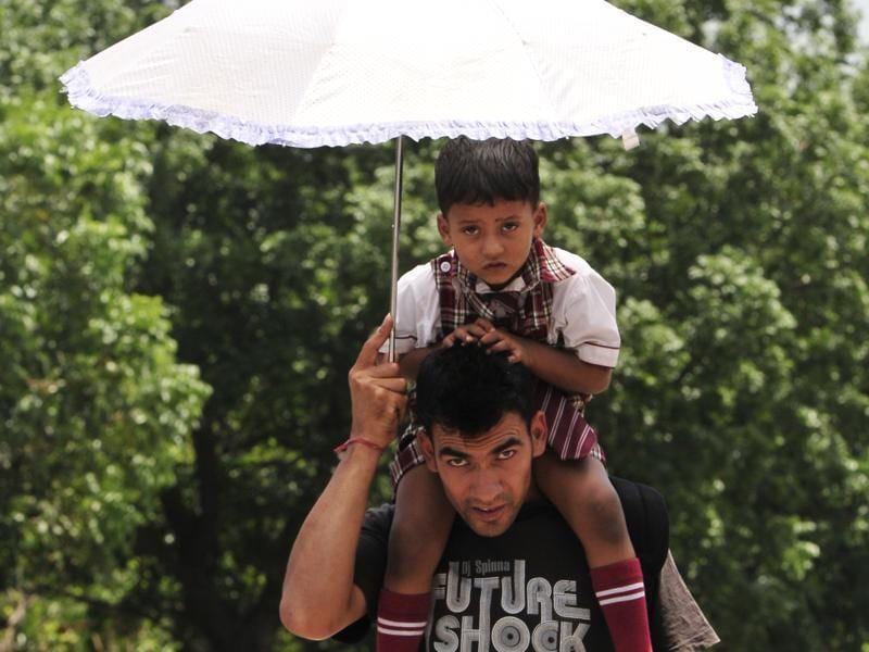 A man and child make do with an umbrella to fight the sun in Mohali on Wednesday. (Keshav Singh/Ht Photo)