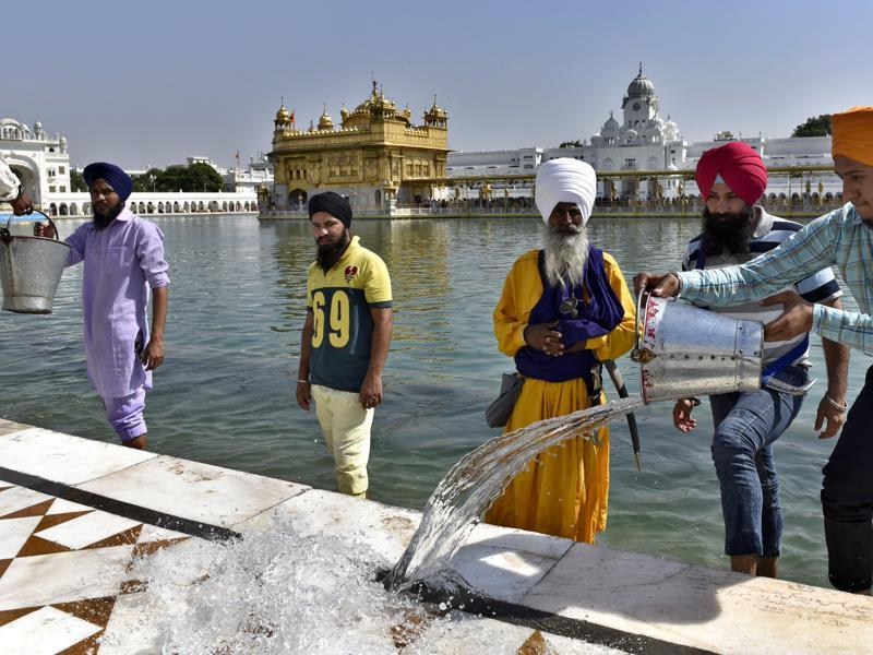 Volunteers splash water on the floor of the parikarma of Golden Temple to help devotees walk easily in the scorching heat, in Amritsar. (Gurpreet Singh/HT Photo)