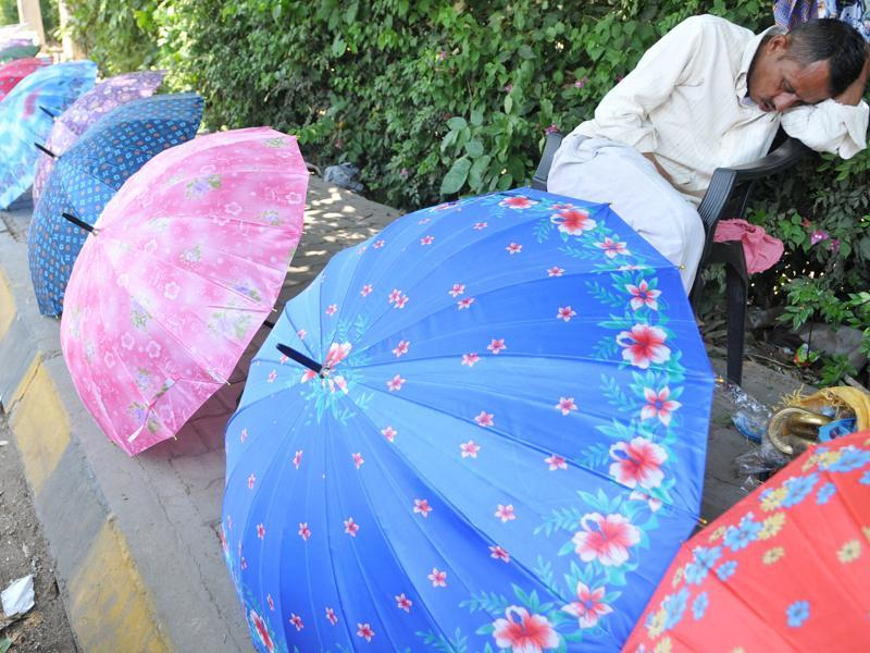 With heat keeping customers away, a roadside umbrella vendor takes a nap in Jalandhar on Wednesday. (Pardeep Pandit/HT Photo)
