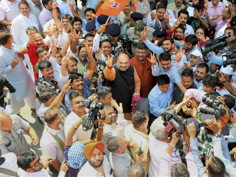 BJP President Amit Shah is welcomed by the party workers as he arrives at the party office in New Delhi on Thursday to address the media following the results of Assembly elections in the five states.  (PTI)