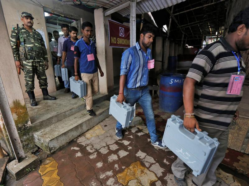 Election officials carry electronic voting machines (EVM) as they arrive to count votes in the West Bengal Assembly elections, at a counting center in Kolkata. (REUTERS)