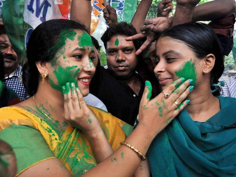 Trinamool Congress workers smear color on each other as they celebrate the party's thumping victory in West Bengal Assembly elections, in Kolkata on Thursday.  (PTI)