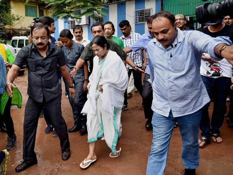 Escorted by her security personnel, West Bengal CM Mamata Banerjee walks out of her residence after her party's thumping win in West Bengal Assembly elections. (PTI )