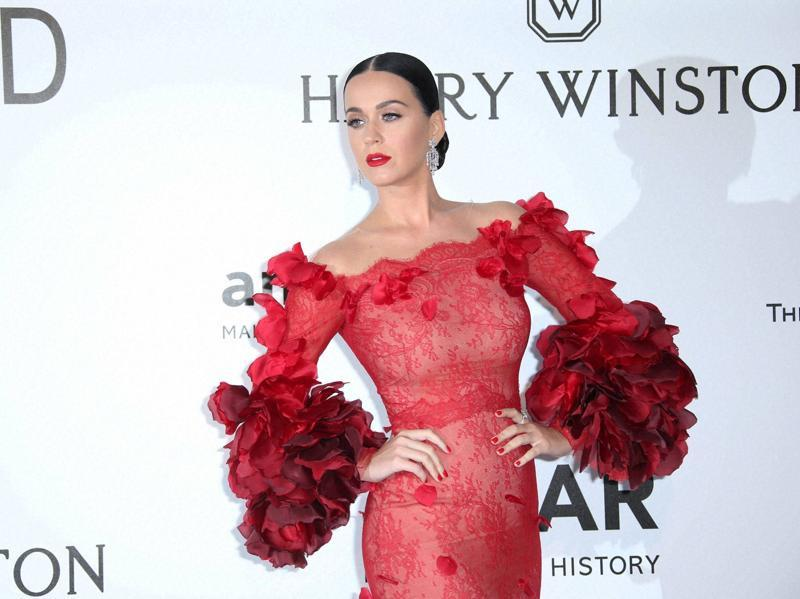Singer Katy Perry poses for photographers in a very flamenco inspired dress with her dark hair slick back and in a bun. (AP)