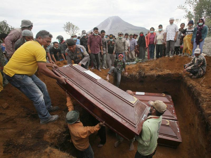 Coffins containing the bodies of the victims in the eruption of Mount Sinabung are lowered into a grave during a funeral in Sukandebi, North Sumatra, Indonesia, Sunday, May 22, 2016. (AP)