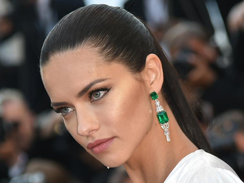 Adriana Lima: The model picked diamonds and emeralds to accessorize her white dress, with a pair of Chopard earrings. (AFP)