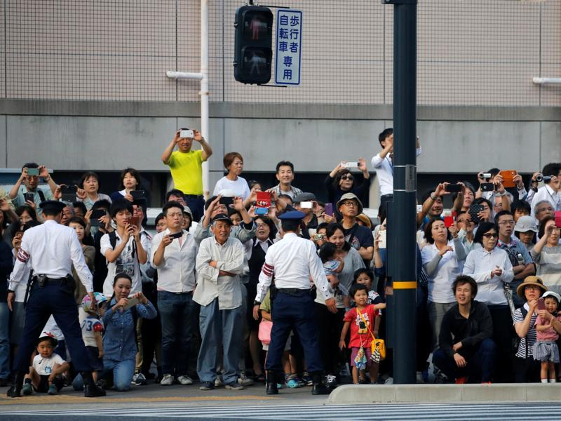 Hiroshima residents watch the motorcade carrying Obama as police officers stand guard enroute to Hiroshima Peace Memorial Park. (REUTERS)
