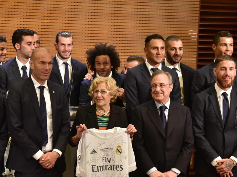 Mayor of Madrid, Manuela Carmena (C), poses with a Real Madrid jersey surrounded by the team in Madrid town hall on May 29. (AFP Photo)