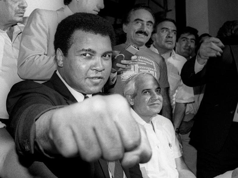 A smiling Muhammad Ali shows his fist to reporters during an impromptu news conference in Mexico City. (Reuters Photo)
