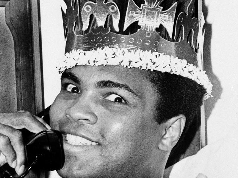 Muhammad Ali speaks on the phone while wearing a king's crown in Miami Beach.  (AP photo)