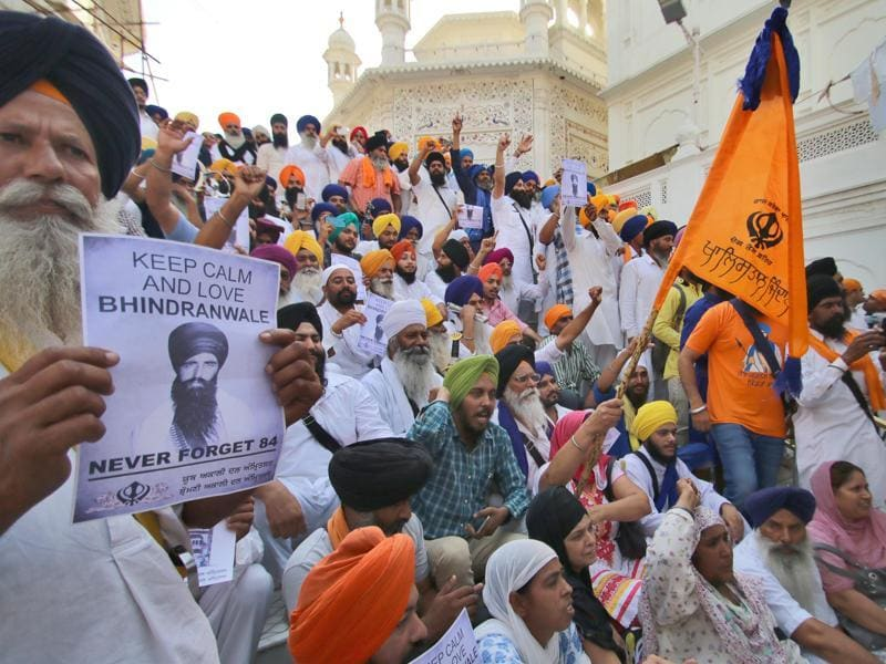 An activist of the Sikh radical group holding a poster of Jarnail Singh Bhindranwale as  the others raise slogans at the Golden Temple in Amritsar on Monday. (Gurpreet Singh/HT)
