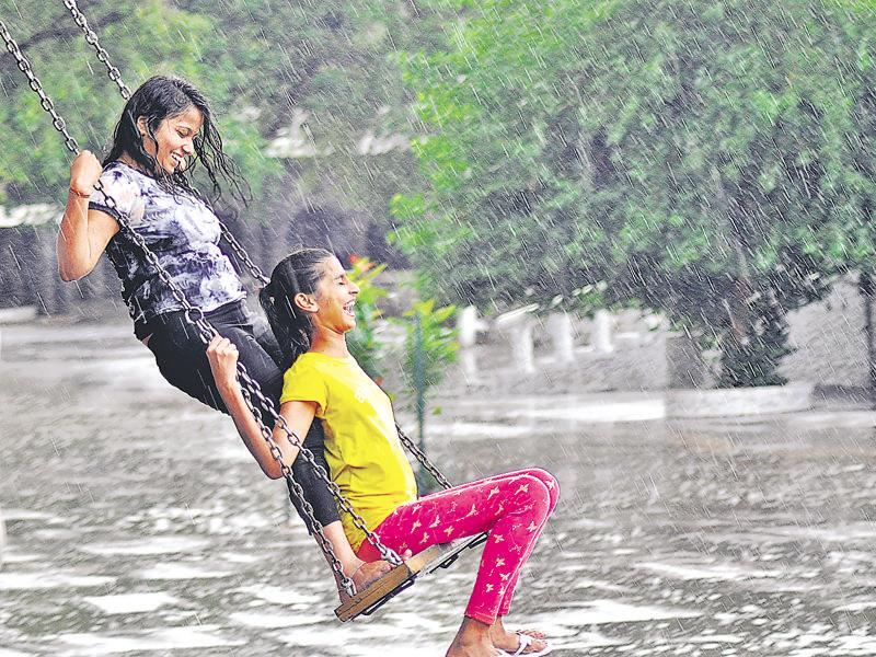 Girls having fun on a swing as the rain gods gave Chandigarh residents a pleasant surprise on Tuesday.  (Karun Sharma/ HT Photo)