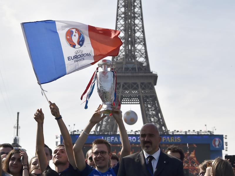 Fans hold up French flags with the Euro 2016 logo as well as replicas of the trophy during the concert. (AFP)