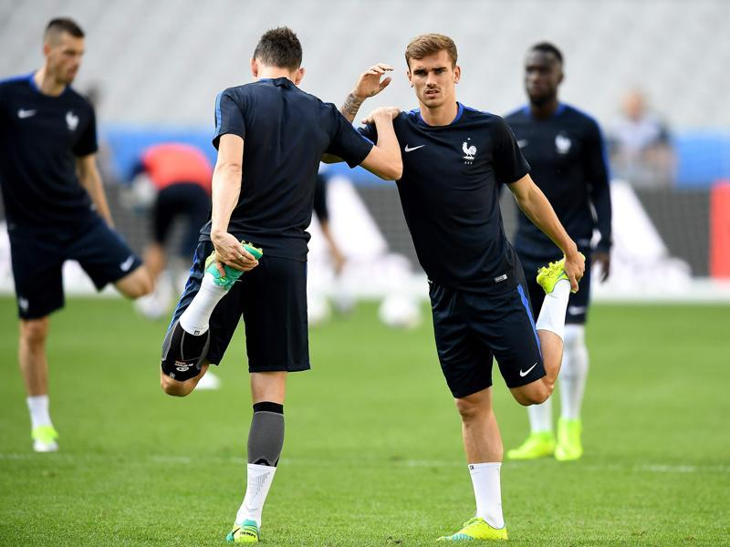 Antoine Griezmann (R) and Laurent Koscielny help each other stretch. (AFP)