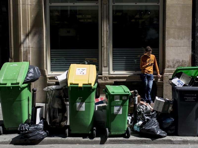 A man rests past overflowing garbage cans and rubbish bags in Paris. (AP Photo)