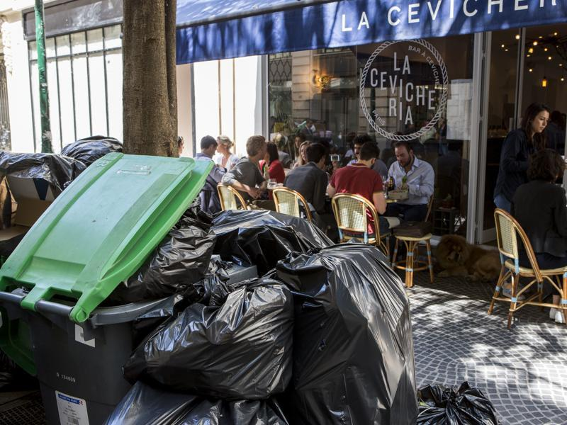 People have lunch past overflowing garbage cans and rubbish bags in Paris, France. (AP Photo)
