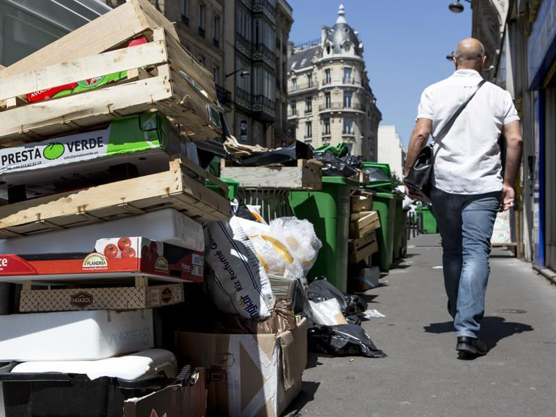 A man walks past an overflowing pile of rubbish bags in Paris, France. (AP Photo)