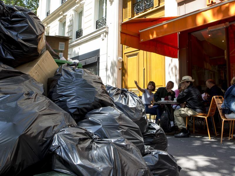 French authorities have sent in private rubbish collection trucks to clear piles of rotting garbage from Paris streets. (AP Photo)
