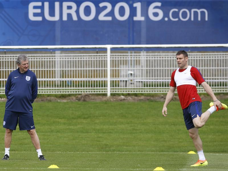 James Milner stretches under the watchful eye of England coach Roy Hodgson. (AP)