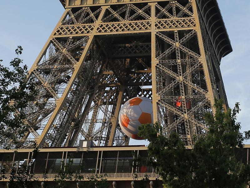 A giant football hangs under the Eiffel Tower as part of the  run-up to Euro 2016. (AP)