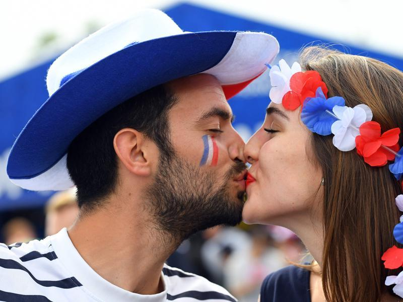 A man and a woman supporting France kiss prior to the Euro 2016 group A football match between France and Romania at Stade de France, in Saint-Denis. (AFP)