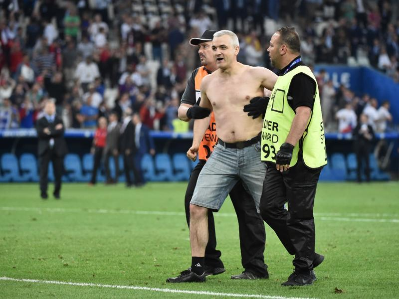 A Russia supporter is escorted off the pitch by stewards. (AFP)