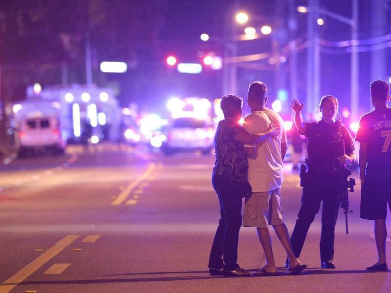 Orlando Police officers direct family members away from a fatal shooting at Pulse Orlando nightclub in Orlando on Sunday. (AP)