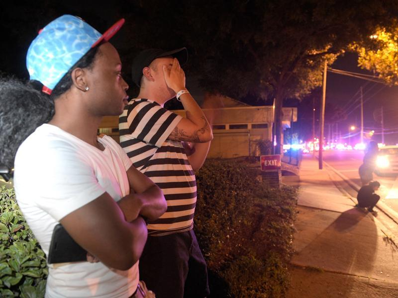 Jermaine Towns, left, and Brandon Shuford wait down the street from a multiple shooting at a nightclub in Orlando, on Sunday. (AP)